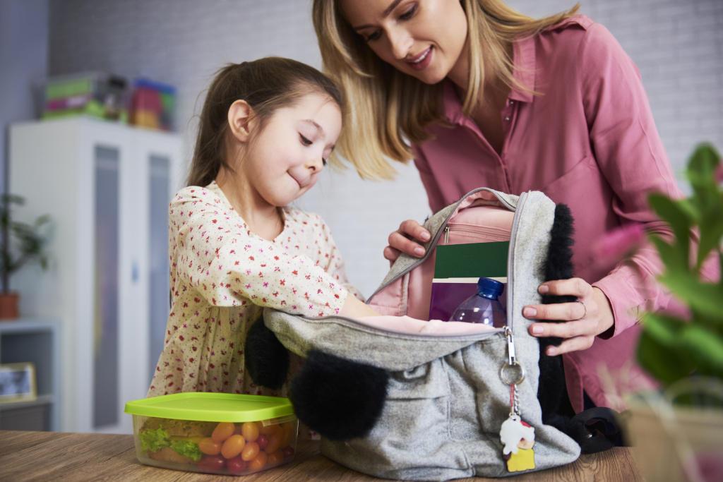 Niña preparando la mochila con su madre, incluyendo el desayuno