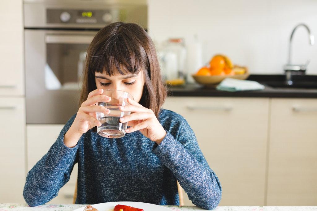 Niña bebiendo agua en la cocina