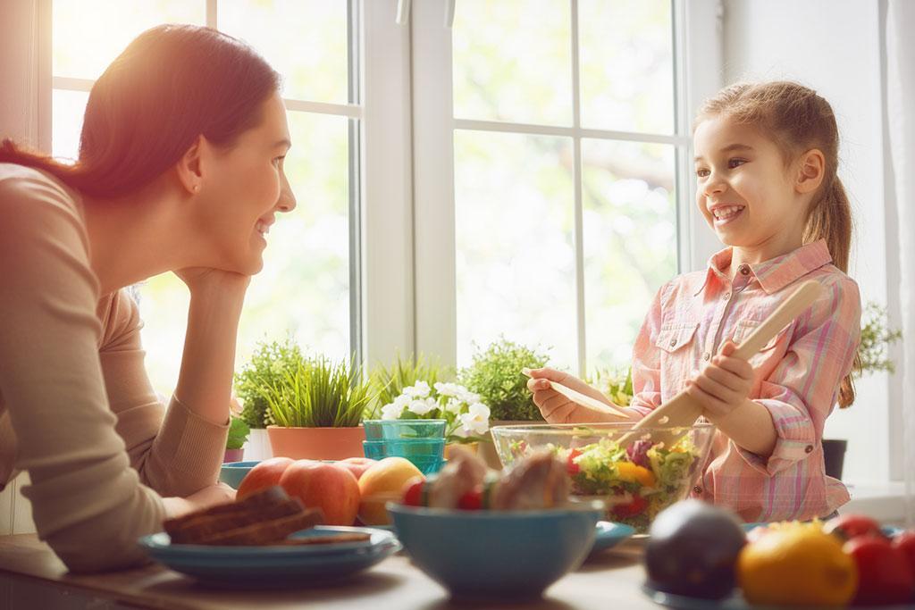 Madre e hija preparando una ensalada juntas