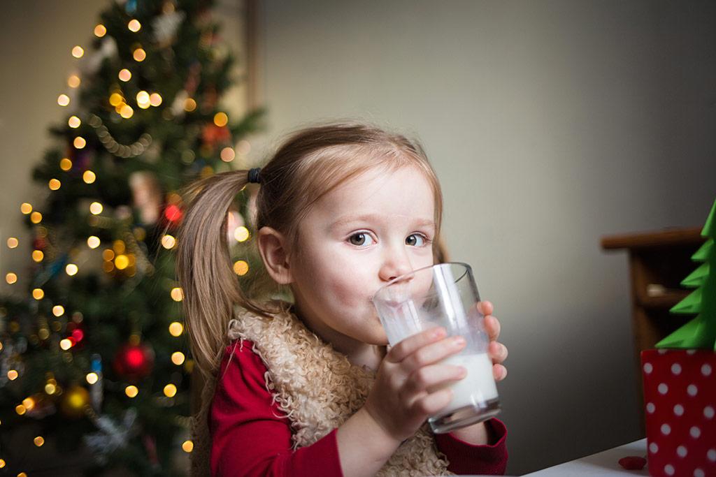 Niña bebiendo leche junto al árbol de Navidad