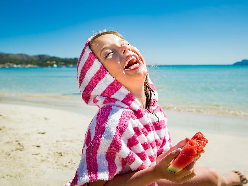 Niña en la playa comiendo sandía